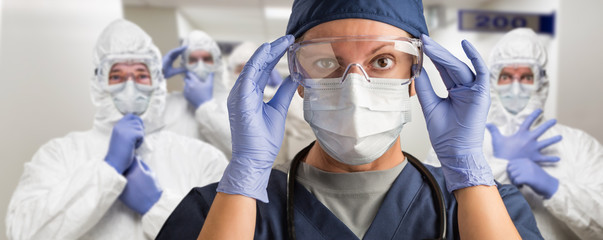 Team of Female and Male Doctors or Nurses Wearing Personal Protective Equiment In Hospital Hallway