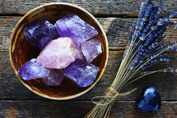Fototapeta A table top image of a pottery bowl with large rose quartz and amethyst crystal with dried lavender flowers. obraz