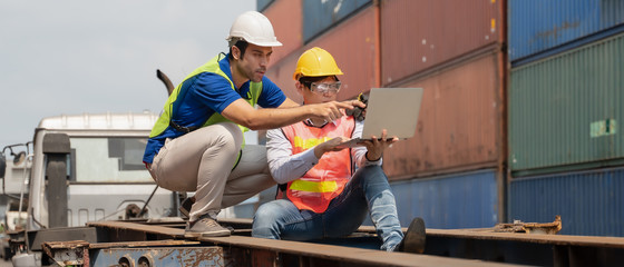 industrial background of caucasian containers yard and cargo loading controller and asian inspector working together on container truck at containers loading area outdoors