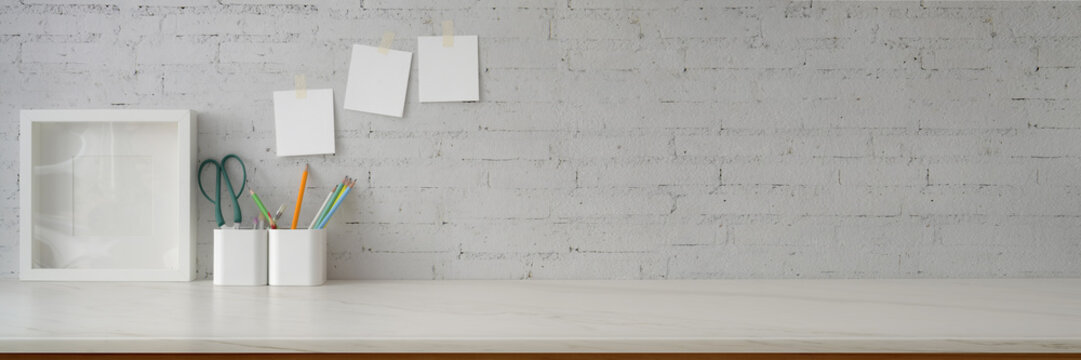 Cropped shot of minimal workspace with mock-up frame, supplies, stationery and copy space
