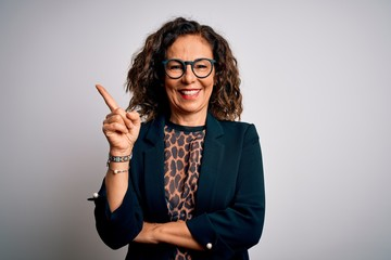 Wall Mural - Middle age brunette business woman wearing glasses standing over isolated white background with a big smile on face, pointing with hand and finger to the side looking at the camera.