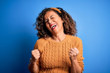 Wall Mural - Middle age beautiful woman wearing casual yellow sweater over isolated yellow background excited for success with arms raised and eyes closed celebrating victory smiling. Winner concept.