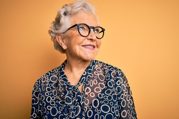 Senior beautiful grey-haired woman wearing casual shirt and glasses over yellow background looking away to side with smile on face, natural expression. Laughing confident.