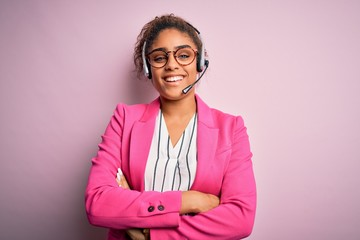 Young african american call center agent girl wearing glasses working using headset happy face smiling with crossed arms looking at the camera. Positive person.