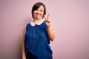 Young down syndrome woman wearing elegant shirt over pink background smiling with happy face winking at the camera doing victory sign. Number two. Fotobehang