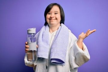 Young down syndrome fitness woman training at gym holding water bottle and sport towel very happy and excited, winner expression celebrating victory screaming with big smile and raised hands