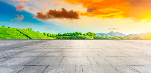 Empty square floor and green tea plantation nature landscape at sunset.