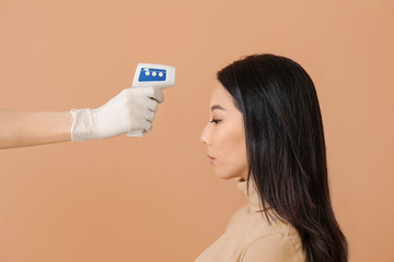 Doctor measuring temperature of Asian woman on color background. Concept of Coronavirus epidemic