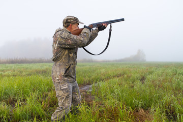 a man takes aim with a rifle in a meadow on a foggy morning