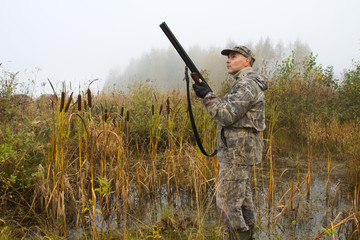 the hunter with a gun prepared to shoot the ducks
