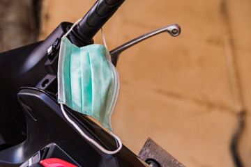 Used surgical mask hangs on a motorcycle handlebar. This is to illustrate the scarcity of medical equipment when a coronavirus outbreak caused a worldwide crisis.