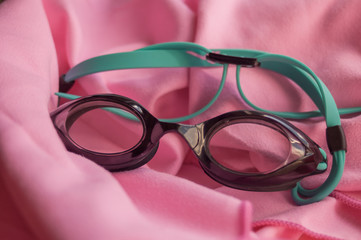 Close-up of black diving goggles on a pink microfiber towel with natural lighting