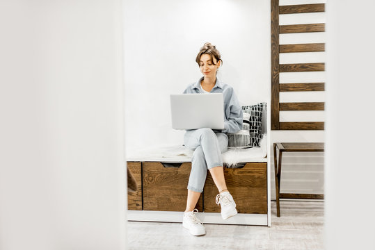 Young woman working on laptop while sitting on the comfortable bed at home. Work online from home at cozy atmosphere concept