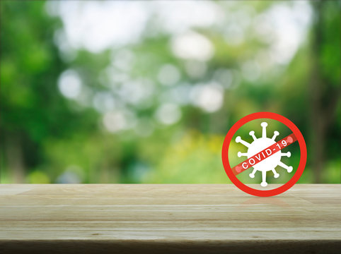 Stop COVID-19 outbreak icon on wooden table over blur green tree in park, Concept of novel coronavirus outbreak