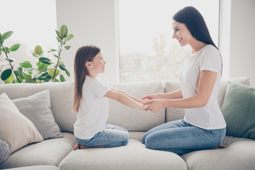 Profile photo of pretty little girl young charming mommy holding arms hands having fun looking eyes sitting comfy sofa spend time weekend together indoors home house Wall mural