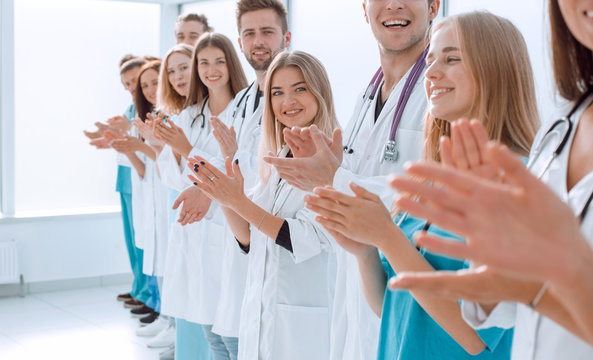 top view. a group of smiling doctors pointing at you.