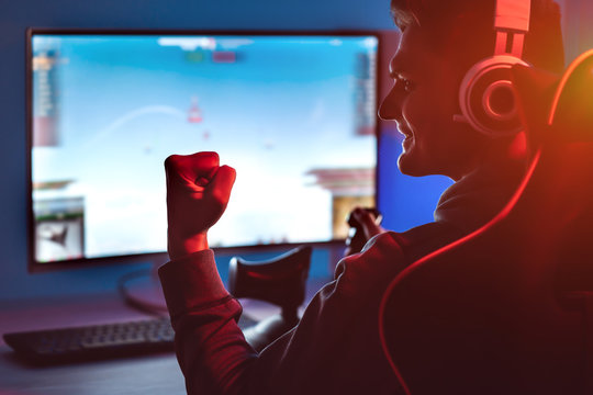 The guy gamer with headset playing video games on his personal computer