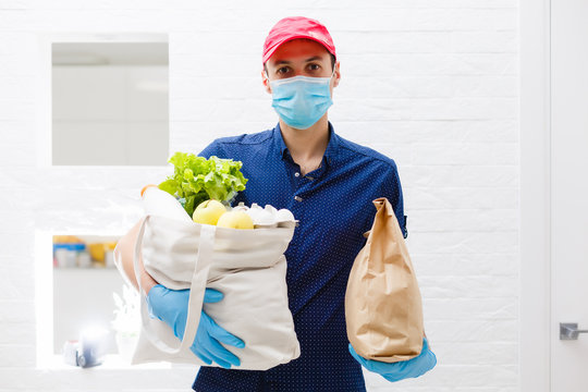 Courier's hands in latex white medical gloves deliver parcels in food packages to the door during the epidemic of coronovirus, COVID-19. Safe delivery of online orders during the epidemic.