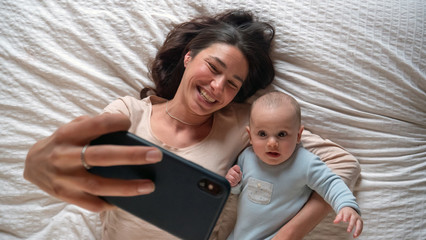 Authentic close up of neo mother and her newborn baby making a selfie or video call to father or...