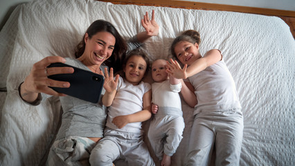Authentic shot of happy mother with her kids are making a selfie or video call to father or relatives in a bed. Concept of technology, new generation,family, connection, parenthood, authenticity Fotobehang
