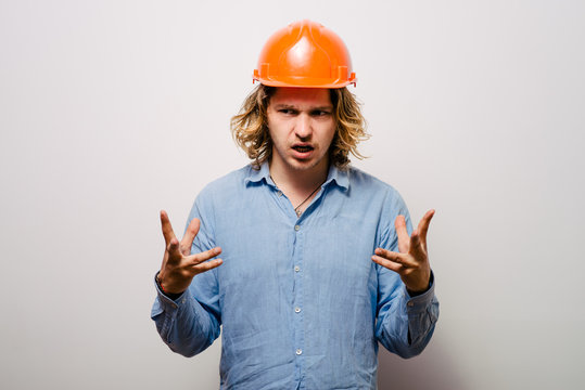 A portrait of an angry male construction worker wearing a safety gear