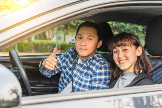 Young asian couple happiness sitting in car show thumb up. Travel concept, Safety first insurance concept, New car concept
