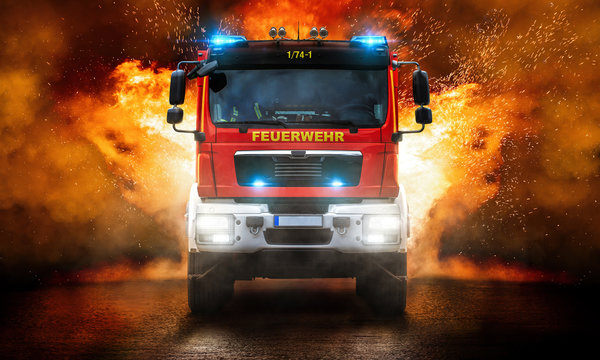 Feuerwehrfahrzeug mit Blaulicht und mit Flammen im Hintergrund