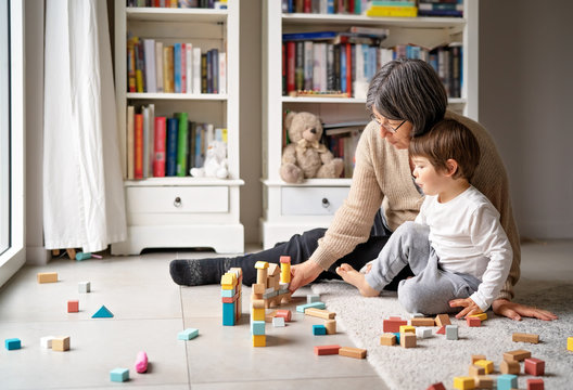 Little toddler boy playing wooden building blocks with grandmother at home. Family spending time together at quarantine period during pandemic. Bright lifestyle.