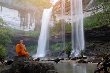 Buddha monk practice meditation with waterfall