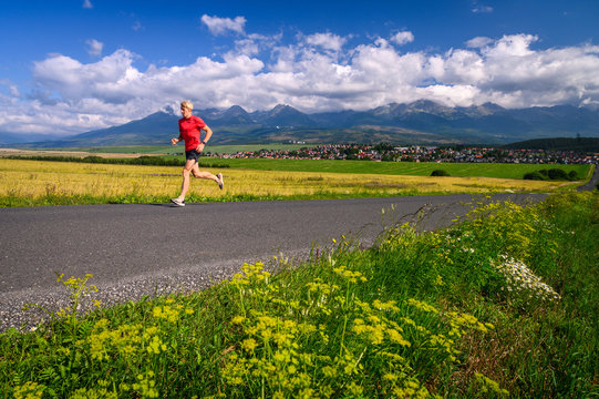 Long distance runner train on the road under big mountains. Summer day