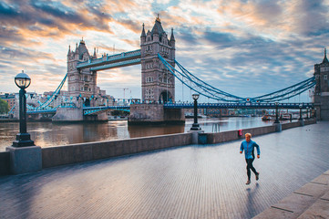 Tuinposter Londen Alone runner in empty streets of london in Coronavirus, Covid-19 quarantine time. Tower Bridge in background