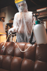 Person with protective antiviral mask, chemical decontamination sprayer bottle disinfecting...