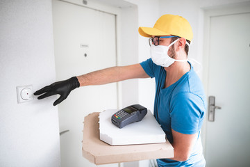 Deliveryman with protective medical mask holding pizza box and POS wireless terminal for card...
