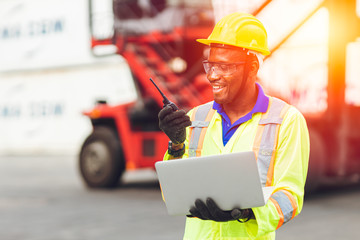 Black African happy worker working in logistic communication using radio and laptop to control loading containers at port cargo to trucks for export and import goods. Wall mural