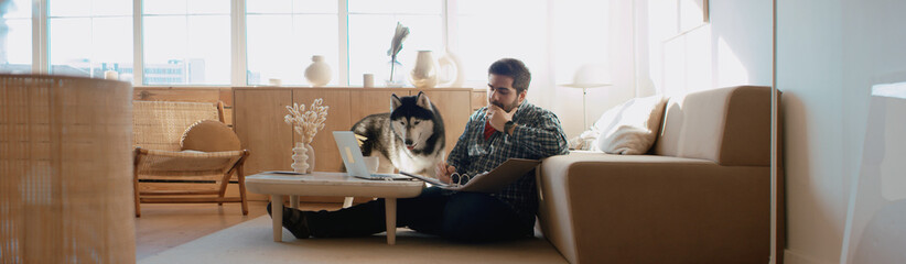 Middle Eastern male working from home, having a video call, dog sits near him. Stay home,...