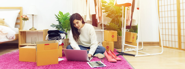 work from home. happy female selling products online, start up small business owner using laptop computer on wooden floor with fashion clothes accessories and postal parcel in her room Wall mural