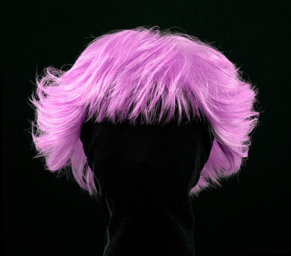 Pink hair wig isolated on black background