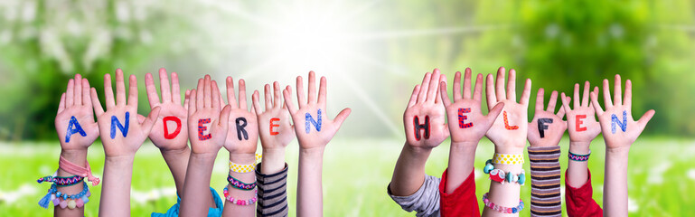 Kids Hands Holding Colorful German Word Anderen Helfen Means Help Others. Sunny Green Grass Meadow As Background