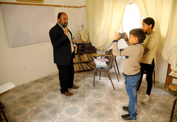 Palestinian Arabic language teacher is filmed by his son as he records an online class to his students, in the Israeli-occupied West Bank
