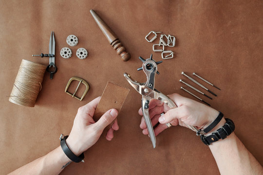 Top view of master hands in bracelets holding hand tool for making holes