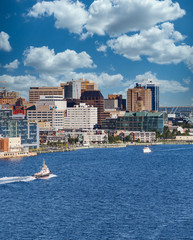 Wall Mural - A tugboat sailing past the city of Halifax, Nova Scotia in blue water