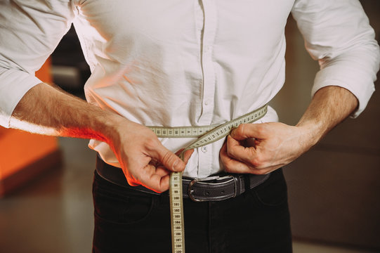 A man in a shirt holds a measuring tape. losing weight
