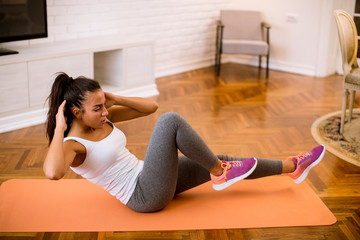 Attractive female doing exercise in her living room