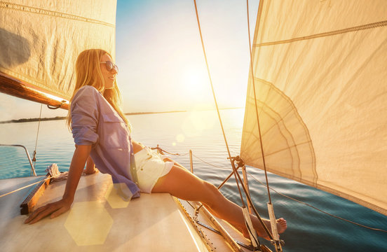 Young happy woman enjoying sunset from deck of sailing boat movi