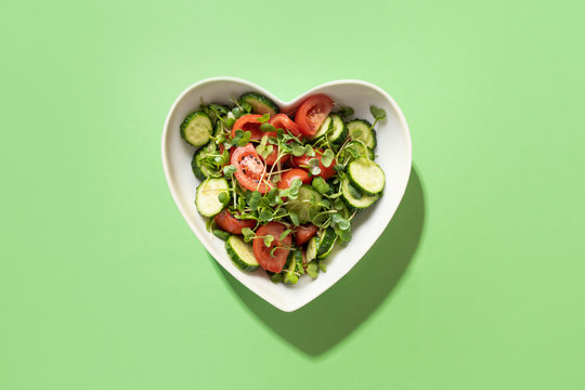Fresh salad with tomato, cucumber, vegetables, microgreen radishes in plate shape of heart on green. View from above. Concept vegan and healthy eating.