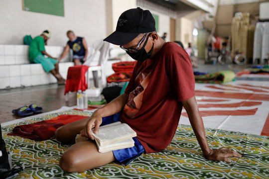 A man wearing a protective face mask reads a book while others play a board game in gymnasium which turned into a shelter for the homeless following the enforcement of a community quarantine in Manila