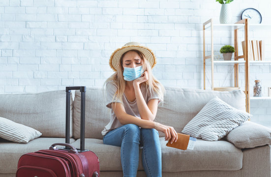 Quarantine concept. Sad girl with suitcase holding passport
