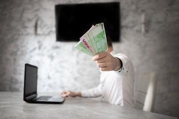 Obraz Biznesmen w biurze, banknoty euro w ręce - fototapety do salonu