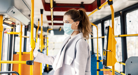 Woman wearing surgical protective mask in a public transportation