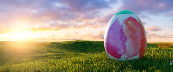 big painted colorful watercolor easter egg at easter on sunrise or sunset on a meadow landscape,...